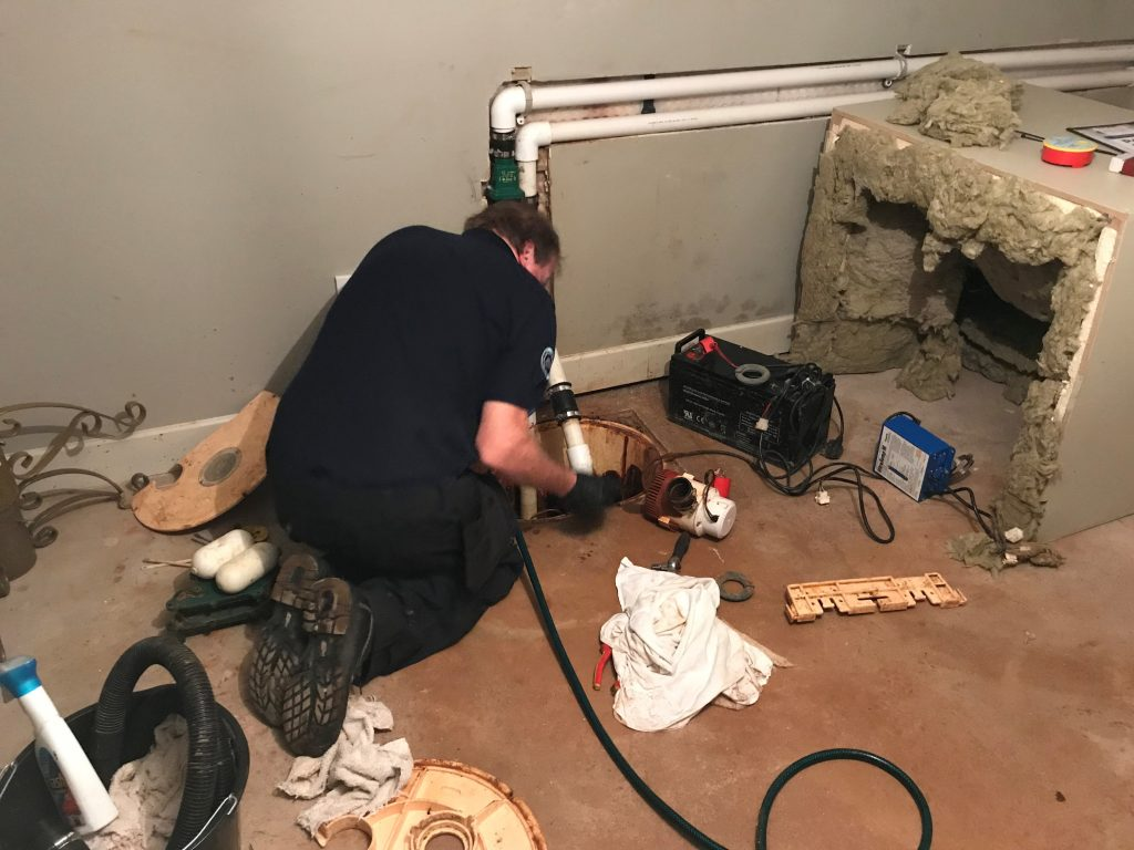 Technician installing sump pump